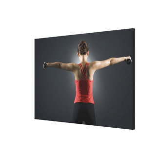 Young woman using dumbbells, rear view, studio canvas print