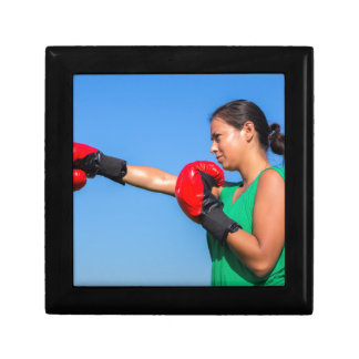 Young woman wearing red boxing gloves blue sky gift box