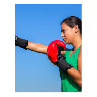 Young woman wearing red boxing gloves blue sky postcard