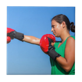 Young woman wearing red boxing gloves blue sky tile