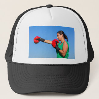 Young woman wearing red boxing gloves blue sky trucker hat