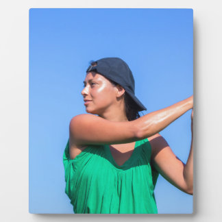 Young woman with baseball bat and cap plaque