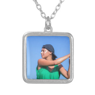 Young woman with baseball bat and cap silver plated necklace