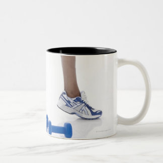 Young woman with dumbbells stretching (low Two-Tone coffee mug